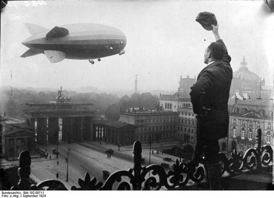 A black and white photograph of an airship flying past a landmark in 1920s Berlin, whilst an onlooker waves his cap.
