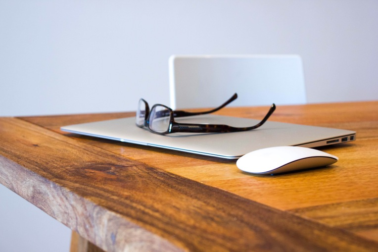 A closed laptop with a mouse and spectacles on a wooden table