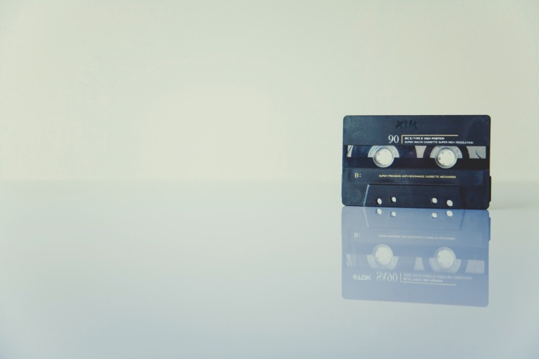 A black cassette tape on a white reflective surface